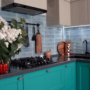 This is an example of a mid-sized beach style l-shaped separate kitchen in Other with an undermount sink, raised-panel cabinets, turquoise cabinets, solid surface benchtops, blue splashback, ceramic splashback, black appliances, porcelain floors, no island, grey floor and grey benchtop.