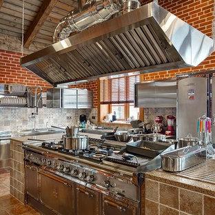 На фото: отдельная кухня в стиле кантри с плоскими фасадами, кухней из нержавеющей стали, серым фартуком, коричневым полом и техникой из нержавеющей стали с