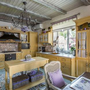 Новые идеи обустройства дома: большая угловая кухня в классическом стиле с обеденным столом, накладной раковиной, фасадами с утопленной филенкой, желтыми фасадами, разноцветным фартуком, черной техникой, островом и бирюзовым полом