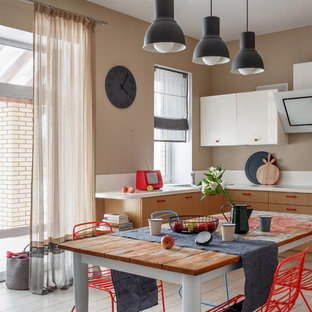 На фото: угловая кухня среднего размера в стиле фьюжн с обеденным столом, фасадами цвета дерева среднего тона, белым фартуком, полом из керамической плитки, бежевым полом, белой столешницей, накладной раковиной и плоскими фасадами без острова с