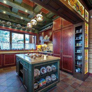 На фото: кухня в стиле кантри с обеденным столом, красными фасадами, столешницей из акрилового камня, островом и техникой под мебельный фасад