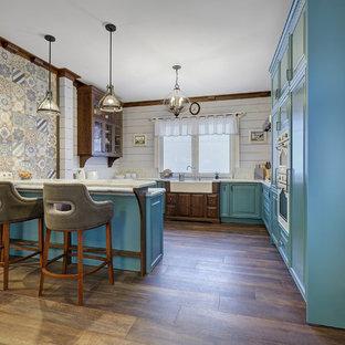 Удачное сочетание для дизайна помещения: п-образная кухня в стиле кантри с раковиной в стиле кантри, фасадами с выступающей филенкой, бирюзовыми фасадами, темным паркетным полом, полуостровом, коричневым полом, белой столешницей, белым фартуком и белой техникой - самое интересное для вас