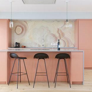 Новый формат декора квартиры: большая параллельная кухня-гостиная в современном стиле с плоскими фасадами, оранжевыми фасадами, столешницей из акрилового камня, желтым фартуком, фартуком из мрамора, техникой из нержавеющей стали, островом, светлым паркетным полом и бежевым полом