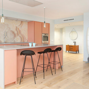 Photo of a mid-sized contemporary galley open plan kitchen in Barcelona with flat-panel cabinets, pink splashback, stainless steel appliances, light hardwood floors, with island and beige floor.
