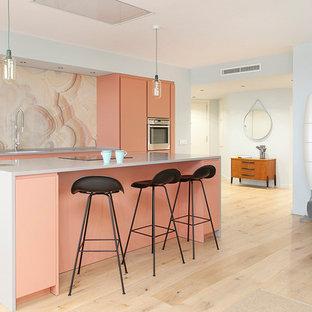 Imagen de cocina de galera, actual, de tamaño medio, abierta, con armarios con paneles lisos, salpicadero rosa, electrodomésticos de acero inoxidable, suelo de madera clara, una isla y suelo beige