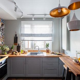 Идея дизайна: маленькая отдельная, угловая кухня в современном стиле с накладной раковиной, фасадами с утопленной филенкой, серыми фасадами, деревянной столешницей, разноцветным фартуком и коричневой столешницей