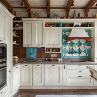 Стильный дизайн: угловая кухня в средиземноморском стиле с монолитной раковиной, фасадами в стиле шейкер, бежевыми фасадами, синим фартуком, техникой под мебельный фасад, полуостровом, коричневым полом и коричневой столешницей - последний тренд