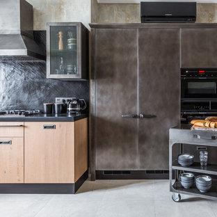 Стильный дизайн: параллельная кухня в стиле лофт с плоскими фасадами, черным фартуком, серыми фасадами, черной техникой и серым полом - последний тренд