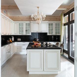 На фото: отдельная кухня в стиле неоклассика (современная классика) с фасадами с выступающей филенкой, белыми фасадами, черным фартуком, бежевым полом и черной столешницей