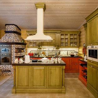 Неиссякаемый источник вдохновения для домашнего уюта: угловая кухня в стиле кантри с фасадами с выступающей филенкой, зелеными фасадами, цветной техникой, островом, коричневым полом и коричневой столешницей