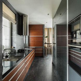 На фото: угловые кухни в современном стиле с врезной раковиной, плоскими фасадами, фасадами цвета дерева среднего тона, серым фартуком, черной техникой, серым полом и черной столешницей