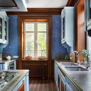 Создайте стильный интерьер: параллельная кухня в стиле рустика с врезной раковиной, серым фартуком, техникой из нержавеющей стали, островом, коричневым полом и серой столешницей - последний тренд
