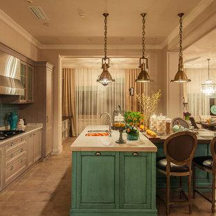 Создайте стильный интерьер: линейная кухня-гостиная в классическом стиле с врезной раковиной, фасадами с утопленной филенкой, бирюзовыми фасадами, синим фартуком, техникой из нержавеющей стали, бежевым полом и белой столешницей - последний тренд