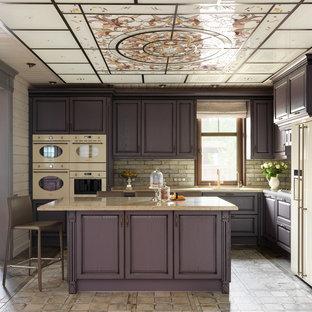 Modelo de cocina en L, clásica renovada, cerrada, con armarios con paneles con relieve, una isla, encimeras beige, fregadero bajoencimera, puertas de armario violetas, salpicadero de azulejos tipo metro y electrodomésticos blancos