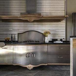 На фото: параллельная кухня в стиле лофт с плоскими фасадами, фасадами из нержавеющей стали, белым фартуком, фартуком из дерева, островом, серым полом и черной столешницей