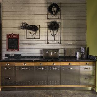 Zweizeilige Industrial Küche mit flächenbündigen Schrankfronten, Edelstahlfronten, Küchenrückwand in Weiß, Rückwand aus Holz, Kücheninsel, schwarzer Arbeitsplatte und grauem Boden in Moskau