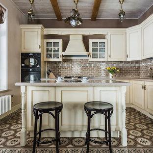 Свежая идея для дизайна: угловая кухня в классическом стиле с фасадами с утопленной филенкой, бежевыми фасадами, коричневым фартуком, фартуком из плитки кабанчик, черной техникой, островом и разноцветным полом - отличное фото интерьера