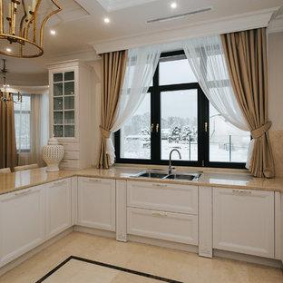 Пример оригинального дизайна интерьера: п-образная кухня среднего размера в стиле современная классика с обеденным столом, бежевым фартуком, фартуком из керамогранитной плитки, островом, накладной раковиной, фасадами с утопленной филенкой, белыми фасадами и бежевой столешницей