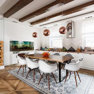 Ejemplo de cocina en L, escandinava, abierta, sin isla, con armarios con paneles con relieve, puertas de armario blancas, salpicadero multicolor y suelo de madera en tonos medios