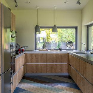 Источник вдохновения для домашнего уюта: п-образная кухня среднего размера в скандинавском стиле с плоскими фасадами, фасадами цвета дерева среднего тона, техникой из нержавеющей стали, разноцветным полом, фартуком с окном, двойной раковиной и серой столешницей без острова