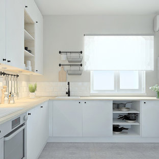 Inspiration for a mid-sized scandinavian l-shaped eat-in kitchen in Other with a single-bowl sink, flat-panel cabinets, white cabinets, wood benchtops, white splashback, stainless steel appliances, porcelain floors, no island, grey floor, beige benchtop and subway tile splashback.