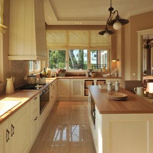 Geschlossene, Mittelgroße Klassische Küche in L-Form mit Kücheninsel, Doppelwaschbecken, Schrankfronten mit vertiefter Füllung, weißen Schränken, Arbeitsplatte aus Holz, Küchenrückwand in Beige, Rückwand aus Mosaikfliesen, schwarzen Elektrogeräten, Keramikboden und beigem Boden