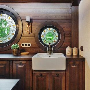 エカテリンブルクのエクレクティックスタイルのおしゃれなキッチン (アンダーカウンターシンク、レイズドパネル扉のキャビネット、茶色いキャビネット、木材カウンター、茶色いキッチンパネル、木材のキッチンパネル、黒い調理設備、磁器タイルの床、茶色い床、茶色いキッチンカウンター) の写真
