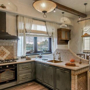 モスクワのシャビーシック調のおしゃれなキッチン (ドロップインシンク、レイズドパネル扉のキャビネット、緑のキャビネット、茶色い床、ベージュのキッチンカウンター、マルチカラーのキッチンパネル、黒い調理設備) の写真