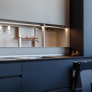 Свежая идея для дизайна: кухня в современном стиле с накладной раковиной, черными фасадами, белым фартуком и черной столешницей - отличное фото интерьера