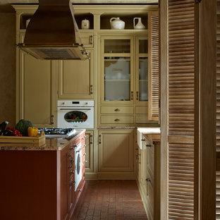 На фото: угловые кухни-гостиные в средиземноморском стиле с раковиной в стиле кантри, кирпичным полом, островом, фасадами с выступающей филенкой и желтыми фасадами