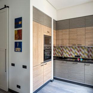 Foto de cocina en L, contemporánea, pequeña, abierta, sin isla, con fregadero integrado, armarios con paneles lisos, encimera de cuarzo compacto, salpicadero multicolor, salpicadero de azulejos de terracota, electrodomésticos de acero inoxidable y suelo laminado
