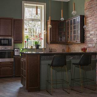 На фото: п-образная кухня в стиле лофт с темными деревянными фасадами, техникой из нержавеющей стали, полуостровом и черной столешницей