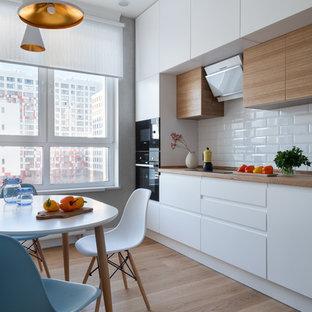 モスクワのコンテンポラリースタイルのおしゃれなダイニングキッチン (フラットパネル扉のキャビネット、白いキャビネット、木材カウンター、白いキッチンパネル、サブウェイタイルのキッチンパネル、黒い調理設備、無垢フローリング、茶色い床、茶色いキッチンカウンター、アイランドなし) の写真