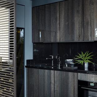 Стильный дизайн: линейная кухня-гостиная в современном стиле с плоскими фасадами, темными деревянными фасадами, черным фартуком, черной техникой и черным полом без острова - последний тренд