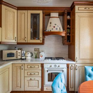 Пример оригинального дизайна: маленькая угловая кухня в классическом стиле с монолитной раковиной, фасадами с выступающей филенкой, светлыми деревянными фасадами, белым фартуком, паркетным полом среднего тона, коричневым полом, белой столешницей и фартуком из каменной плиты