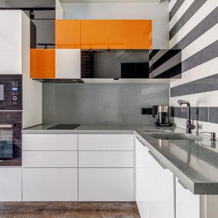 Свежая идея для дизайна: угловая кухня среднего размера в современном стиле с монолитной раковиной, плоскими фасадами, белыми фасадами, серым фартуком, черной техникой, коричневым полом и серой столешницей - отличное фото интерьера