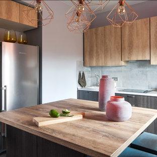 Удачное сочетание для дизайна помещения: угловая кухня-гостиная в современном стиле с плоскими фасадами, светлыми деревянными фасадами, серым фартуком, техникой из нержавеющей стали, островом и коричневой столешницей - самое интересное для вас