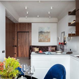 Идея дизайна: маленькая угловая кухня-гостиная в современном стиле с плоскими фасадами, белыми фасадами, врезной раковиной и бежевым полом без острова