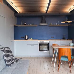 Неиссякаемый источник вдохновения для домашнего уюта: маленькая прямая кухня-гостиная в современном стиле с плоскими фасадами, серыми фасадами, деревянной столешницей, светлым паркетным полом, бежевым полом и коричневой столешницей без острова