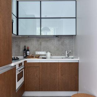 На фото: маленькие угловые кухни в современном стиле с плоскими фасадами, темными деревянными фасадами, серым полом и белой столешницей без острова