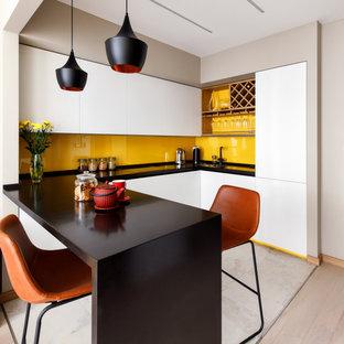 Идея дизайна: п-образная кухня среднего размера в современном стиле с обеденным столом, одинарной раковиной, белыми фасадами, столешницей из акрилового камня, желтым фартуком, фартуком из стекла, техникой под мебельный фасад и черной столешницей