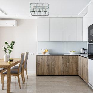 На фото: маленькая угловая кухня-гостиная в современном стиле с одинарной раковиной, белыми фасадами, столешницей из акрилового камня, белым фартуком, фартуком из стекла, техникой под мебельный фасад и белой столешницей без острова с