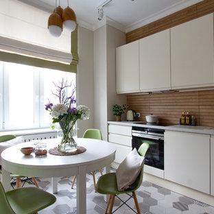 На фото: отдельная, прямая кухня в современном стиле с накладной раковиной, плоскими фасадами, белыми фасадами, коричневым фартуком, черной техникой, серым полом и серой столешницей