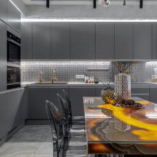 Пример оригинального дизайна: угловая кухня в современном стиле с обеденным столом, накладной раковиной, плоскими фасадами, серыми фасадами, фартуком цвета металлик, фартуком из плитки мозаики, черной техникой, серым полом и серой столешницей