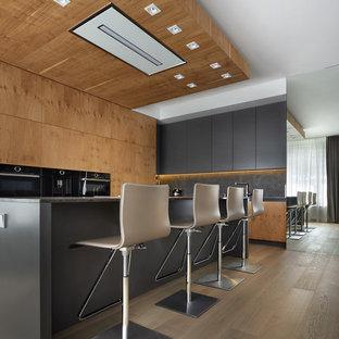 Неиссякаемый источник вдохновения для домашнего уюта: большая угловая кухня-гостиная в современном стиле с плоскими фасадами, черным фартуком, черной техникой, светлым паркетным полом, островом, бежевым полом, черной столешницей и фасадами цвета дерева среднего тона