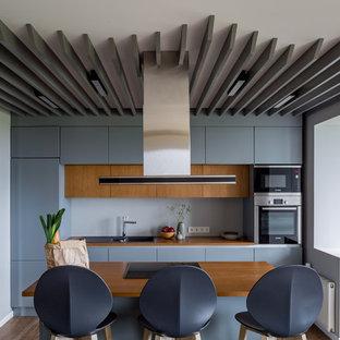 Идея дизайна: параллельная кухня среднего размера в современном стиле с обеденным столом, двумя и более островами, накладной раковиной, плоскими фасадами, синими фасадами, серым фартуком и техникой из нержавеющей стали