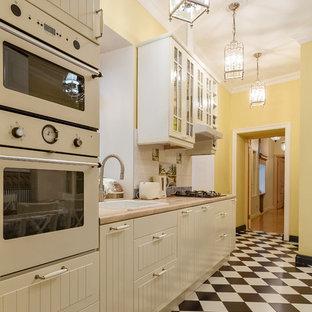 Создайте стильный интерьер: отдельная, линейная кухня в классическом стиле с накладной раковиной, белыми фасадами, белым фартуком и белой техникой без острова - последний тренд