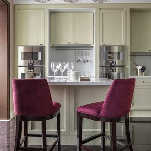Идея дизайна: кухня в стиле современная классика с коричневым полом, фасадами с утопленной филенкой, бежевыми фасадами, белым фартуком, техникой из нержавеющей стали, островом и белой столешницей