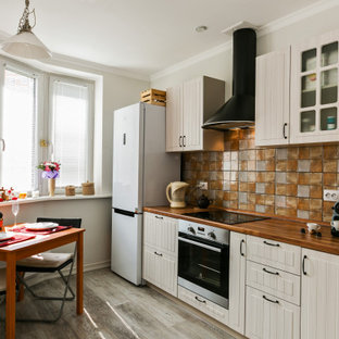 Photo of a traditional single-wall eat-in kitchen in Other with glass-front cabinets, beige cabinets, wood benchtops, multi-coloured splashback, white appliances, no island and brown floor.