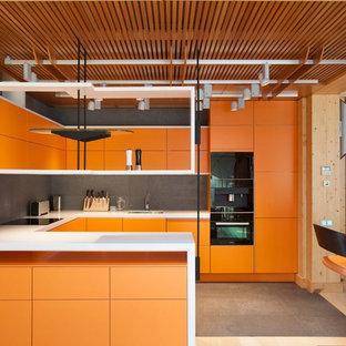 Новые идеи обустройства дома: п-образная кухня-гостиная в современном стиле с врезной раковиной, плоскими фасадами, оранжевыми фасадами, серым фартуком, фартуком из каменной плитки, черной техникой и полуостровом